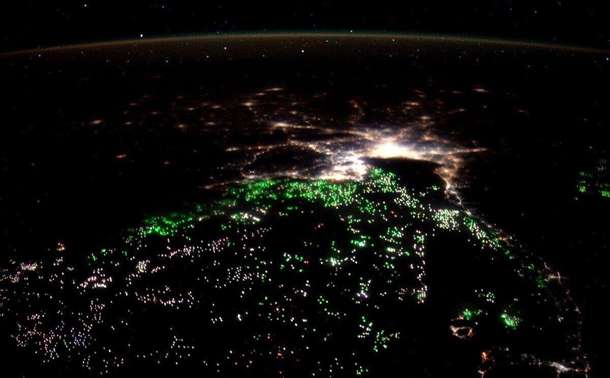 Море освещается зелеными прожекторами рыболовных судов в Сиамском заливе.