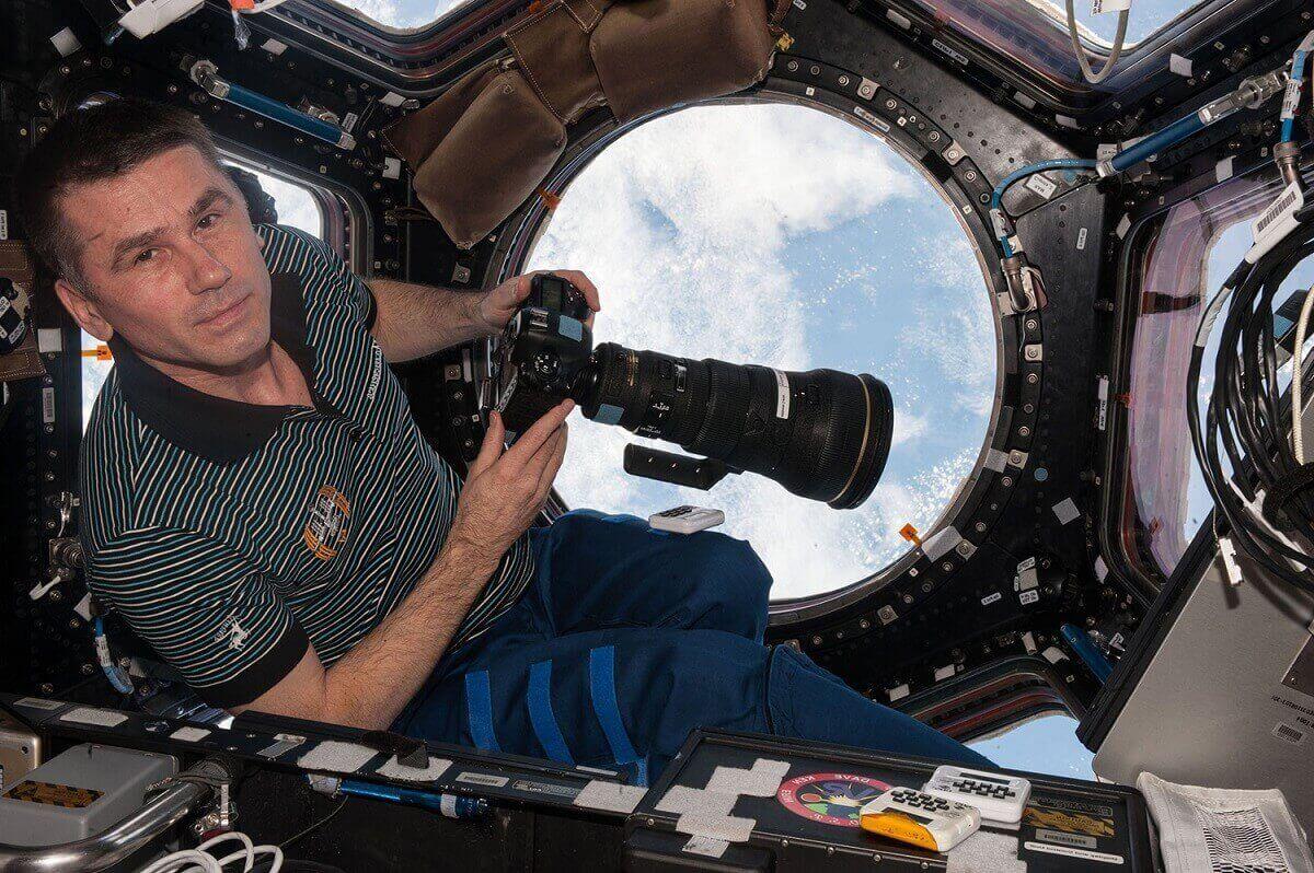 4.Бортинженер программы «Экспедиция 47» Ю.Маленченко в одном из модулей космической станции подготавливается к фотосъемке планеты, используя четырехсот-миллиметровую линзу.