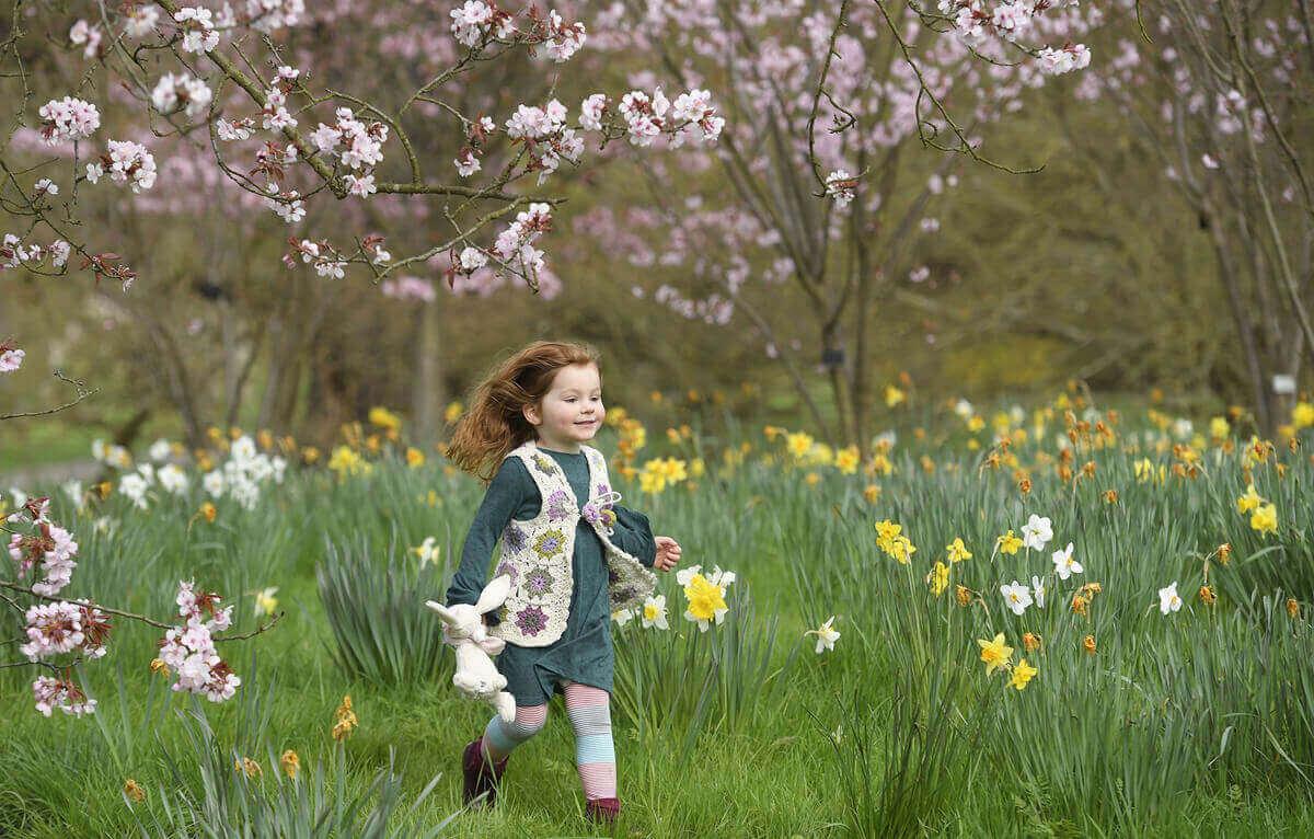 Ева играет среди весенних цветов в Кью-Гарденс в западном Лондоне