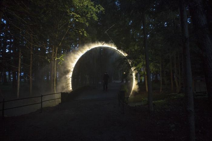 Кольцо водяной дымки окружает мост, пересекающий реку, на фестивале искусств Японских Альп